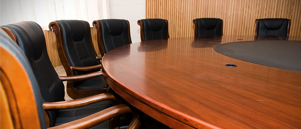 Refinished wooden conference table surrounded by black, leather chairs